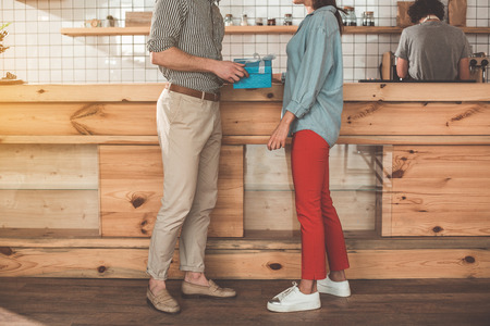 Low angle of loving couple celebrating valentine day in cafeteria. Blue gift box in male hands Stock Photo