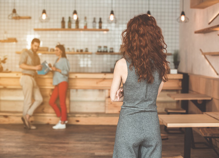 Abused young woman looking at her boyfriend cheating with young girl. She is standing in cafe with crossed hands. Focus on female back