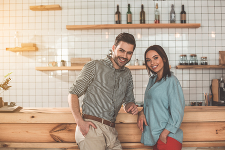Portrait of happy young loving couple are standing near counter in coffee shop. They are looking at camera and smiling