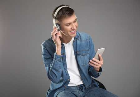 Handsome man with smiling expression sitting and staring at mobile screen. He is having earphones. Isolated on background Imagens