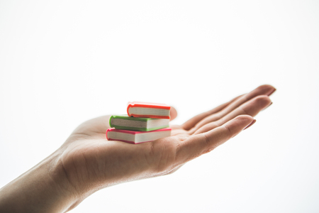 Close up female hand holding colorful pencil erasers. They look like miniature books. It isolated on background. Creativity concept