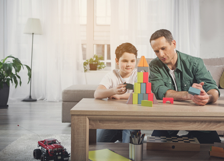 Cheerful father and son are constructing tower by colorful toy blocks. Family entertainment concept Stock Photo