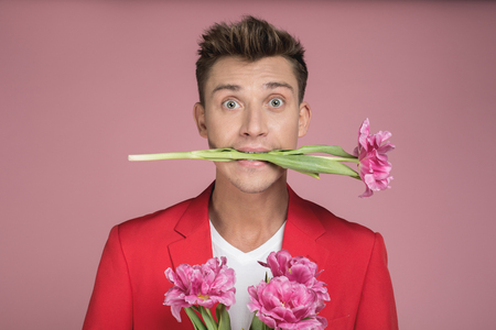 Portrait of young man in red costume with surprised face. He is keeping flowers by mouth. Isolated on background Imagens