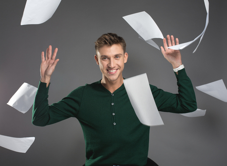 Waist up portrait of satisfied guy tossing away documents in the air while sitting. He is staring at camera with joy. Isolated on background