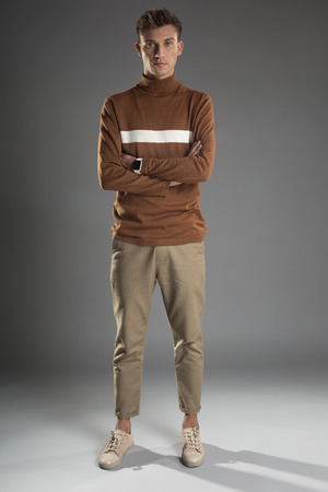 Fashion style concept. Full length portrait of severe young man standing with crossed arms. Gadget is on his wrist