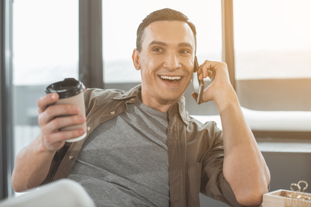 Portrait of beaming worker telling by phone while tasting mug of coffee in office. Happy male resting during labor concept