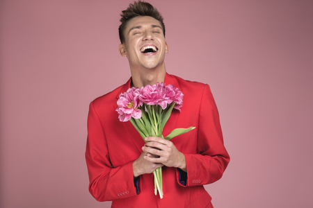 Waist up portrait of glad man in elegant clothes holding tulips with both hands. He is laughing heartily. Isolated on background Standard-Bild - 100125918