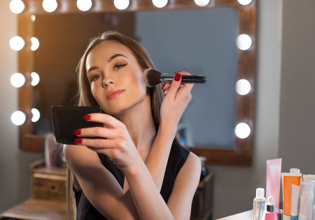 Perfect look. Portrait of attractive young woman is sitting backstage and using brush to apply highlighter. She is looking at camera dreamily Фото со стока