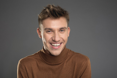 Portrait of cheerful man in pullover staring and laughing. Isolated on background Imagens