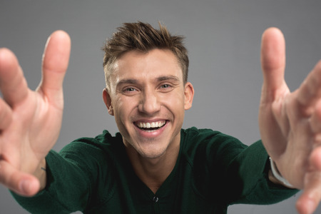 Friendliness concept. Portrait of smiling male person stretching hands to camera. Isolated on background