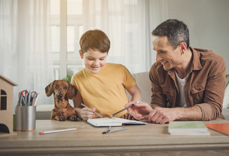 Portrait of happy boy drawing in notebook together with his dad. Playful dog is situating near them
