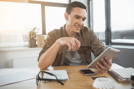 Portrait of happy businessman looking at electronic tablet while sitting at desk in office. Cheerful employer during labor with technology concept Stock Photo