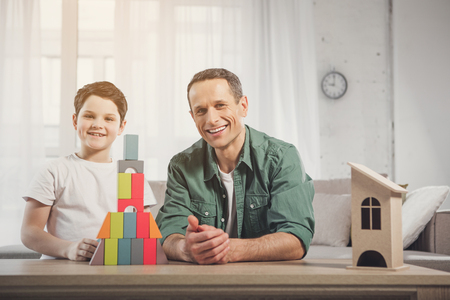 Portrait of cheerful father and son having fun together in house. They are sitting near small toy construction on table and smiling Stock Photo