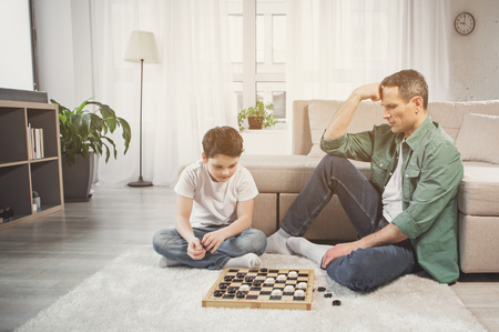 Pensive boy is mulling over next move and looking at chessboard. His father is sitting near him on floor