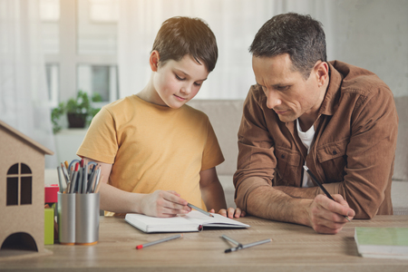Cheerful boy is painting picture with aspiration. His father is looking at paper with interest