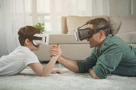 Excited father and son are playing arm-wrestling while using vr headsets. They are lying on floor and smiling 写真素材