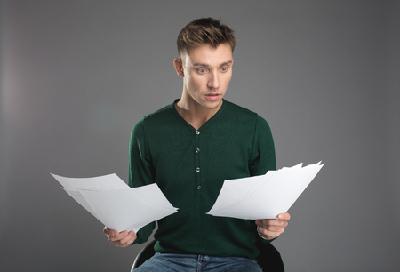 Waist up portrait of shocked male person taking seat on chair and looking at papers in his hands with stun. Isolated on background