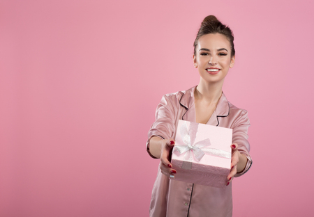 Gift for you. Portrait of cheerful young attractive woman is standing and holding present. She is looking at camera with wide smile. Isolated on pink background and copy space