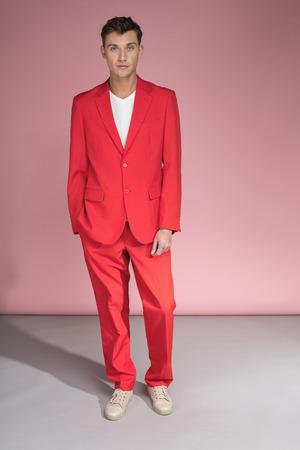 Full length portrait of attractive guy standing in red costume and staring at camera with calmness 写真素材