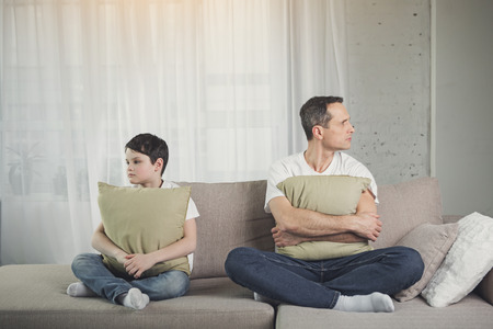 Sad father and son are offended at each other. They are keeping pillows and looking aside while sitting on sofa Stock Photo