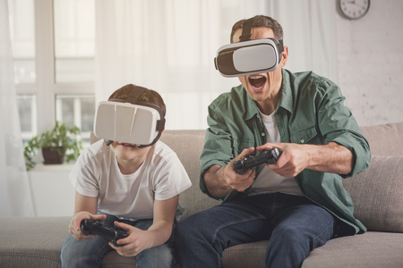 Cheerful family enjoying video game competition. They are holding joysticks and wearing virtual reality gogles Foto de archivo