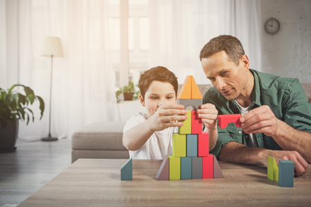 Joyful boy is building toy house with his dad by small details. They are sitting near desk in living room