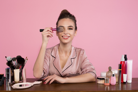 Portrait of optimistic young female cosmetologist is sitting at dressing table with cosmetics items and holding brush. She is looking at camera with smile. Isolated on pink background