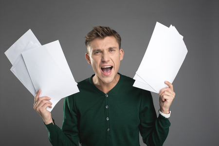 Waist up portrait of angry guy standing with papers in both arms and shouting. Isolated on background Reklamní fotografie