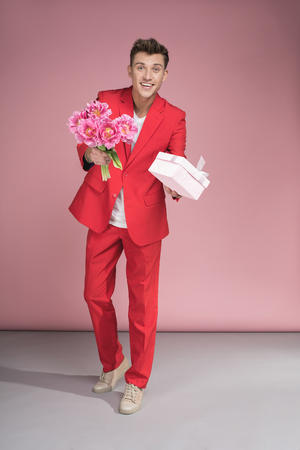 Full length portrait of laughing guy in red suit giving bouquet of flowers and present box Standard-Bild - 100117460