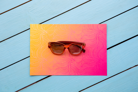 Top view close up of fashionable brown spectacles situating on colorful paper. Style concept