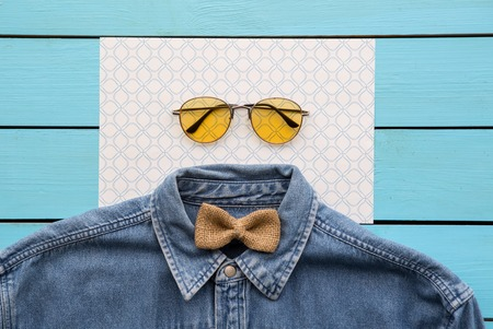 Top view close up of modern shirt, spectacles and casual bowtie situating on paper. Style concept