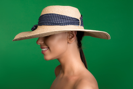 Profile of nude lady standing with hat on head. Isolated on background