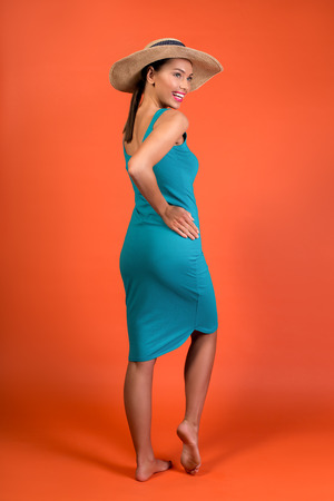 Enjoyed lady standing with her back. She is wearing tight dress and hat Stock Photo