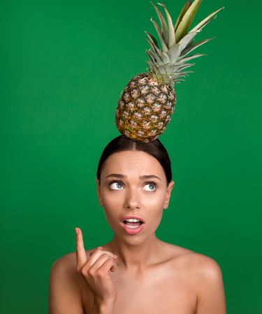 Portrait of bare woman with confused face standing with tropical fruit on her head. She is holding finger up. Isolated on background