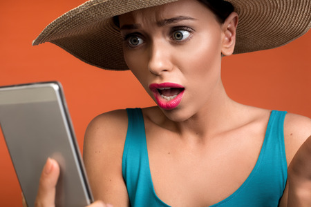 Close up of female person with amazed expression looking at cellphone with daze. Isolated on background