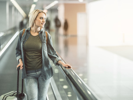 Portrait of thoughtful young lady situating on moving stairs while holding luggage. Contemplative traveler before trip concept. Copy space