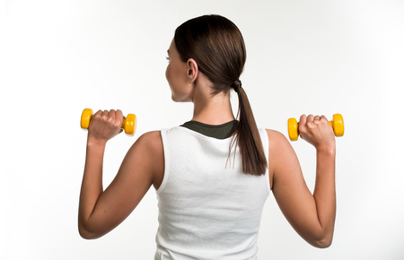 Young girl standing with her back and holding up dumbbell in each hand. Isolated on background Stock Photo