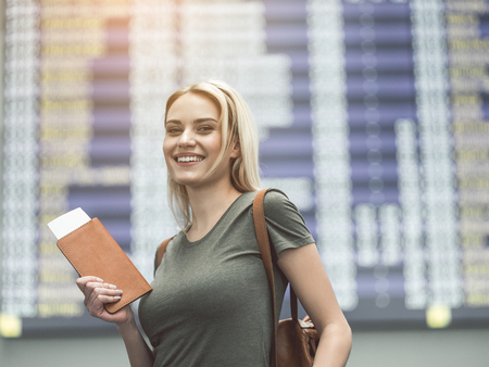 Portrait of cheerful young woman holding password in hands while locating in airport