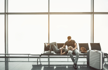 Full length cheerful lady lying on legs of smiling young male in lounge zone in airport. Glad couple resting during waiting of plane concept. Copy space Stock Photo