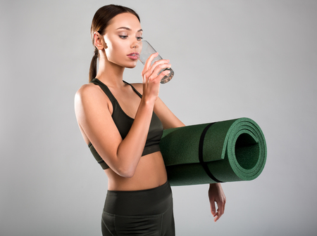 Nice looking woman in sports costume drinking water. She is holding yoga mat under armpit. Isolated on background