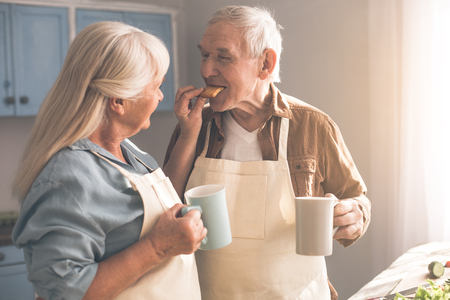 Cheerful mature woman is feeding her husband by cookie and smiling. Man is standing in kitchen and holding a cup of tea