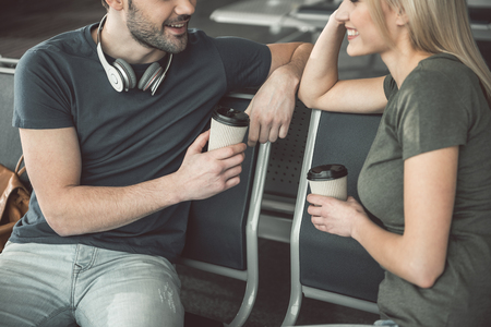 Outgoing man speaking with happy girl while drinking cup of coffee. Satisfied comrades during communication concept