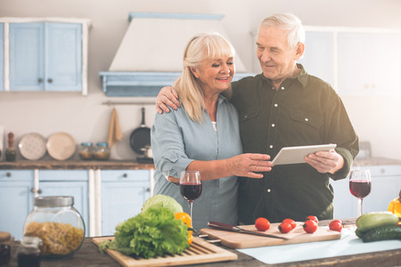 Best moments together. Portrait of happy old loving couple cooking romantic dinner and smiling. They are using tablet and cuddling Stock Photo