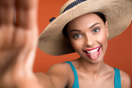 Portrait of humorous woman in hat showing tongue at camera and stretching arm forwards. Focus on face. Isolated on background