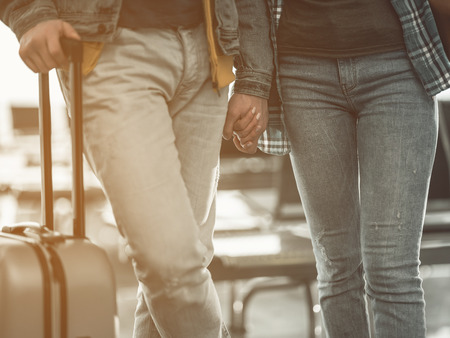 Close up man holding hand of female. They walking in airport. Couple during journey concept Stock Photo