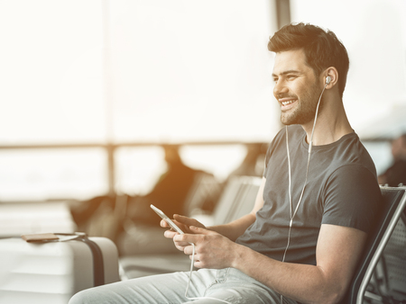 Portrait of laughing man hearing song with headset while using digital device. Leisure concept
