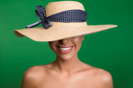 Undressed woman standing with hat on her head and smiling. Isolated on background