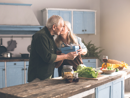 Thank you for wonderful present. Grateful senior woman is kissing her husband cheek while standing in kitchen. Man is smiling with happiness