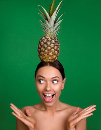 Portrait of naked girl with astonished expression keeping pineapple on the top of her head. Isolated on background