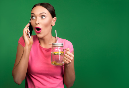 Waist up portrait of appealing lady with cold beverage in hand speaking by cellphone. Her face is stunned. Copy space in right side. Isolated on background